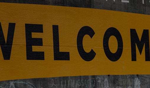 The word welcome written on a wall in black on a yellow background