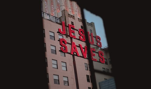 A dark room with a window that shows a signs which says Jesus Saves