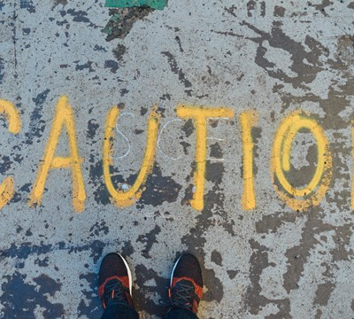 A picture of a persons shoes on the ground that stands in front of the word caution, spray painted on the floor