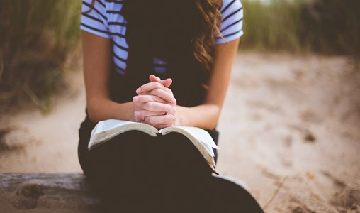 A woman sitting and praying with an open bible